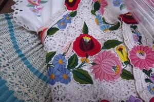 détail de jupe plissée bleue turquoise et d'un gilet brodé et ajouré