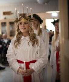 Ste Lucie, une robe blanche et une ceinture rouge